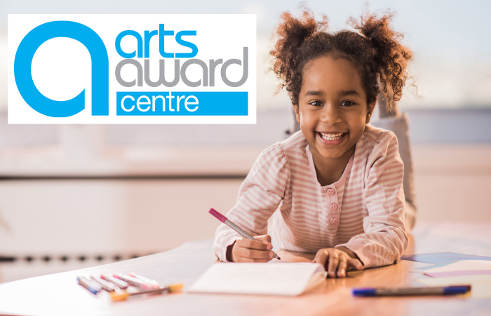 Image of a smiling little black girl with hair in two puffs writing at a desk, top left logo for Arts Award Centre
