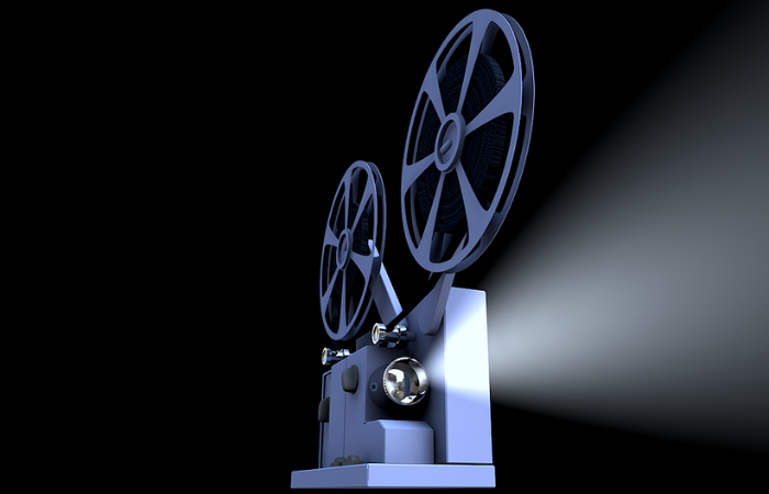 Image of an old style movie projector shining light towards the viewer